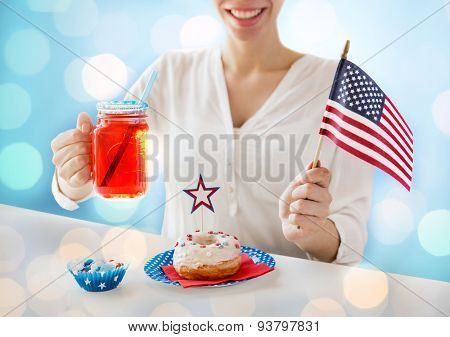 independence day, celebration, patriotism and holidays concept - close up of happy woman with donut celebrating 4th july, holding american flag and drinking juice over blue lights background