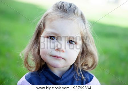 Cute little blonde girl looking at camera with grass of background