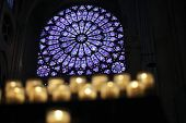 stock photo of stained glass  - Praying candles in front of big stained glass window in the Notre Dame - JPG