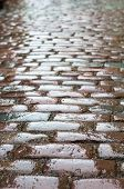 stock photo of cobblestone  - Wet vintage cobblestone road vertical blurred view - JPG