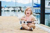pic of ukulele  - Little happy boy plays his guitar or ukulele - JPG