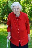 image of handicapped  - Handicap elderly woman using a crutch to walk - JPG