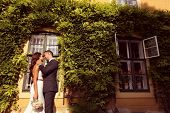 stock photo of ivy  - Bride and groom embracing in front of a beautiful house covered with ivy