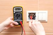 pic of  multimeter  - Hand electrician with multimeter checking voltage - JPG