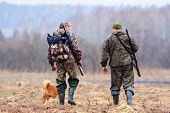 foto of hunter  - two hunters and dog on the field - JPG