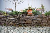 foto of cactus  - Vacant wrought iron table and chairs on an outdoor patio standing on paving alongside a walled rock garden with a potted cactus on the wall - JPG