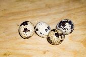 stock photo of quail  - Macro of quail eggs on wooden cutting board background - JPG
