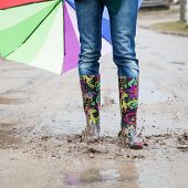 foto of woman boots  - Woman with rain boots jumps into a puddle - JPG