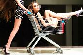 foto of trolley  - Two cute winning women in dresses with shopping trolley indoor on shop background horizontal picture - JPG