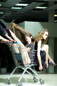 stock photo of trolley  - Two young sexual playful fashionable girls in dresses with shopping trolley indoor on store backdrop vertical picture - JPG