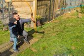 foto of shoot out  - Father and son shoot arrows at a target - JPG