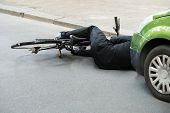 stock photo of accident victim  - Unconscious Male Cyclist Lying On Road After Road Accident - JPG