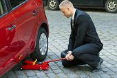 stock photo of hydraulics  - Man Trying To Lift The Car With Red Hydraulic Floor Jack For Repairing - JPG