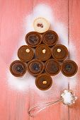 picture of hazelnut tree  - chocolate tartlets in christmas tree shape on pink wooden table - JPG