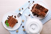 foto of teapot  - Tasty pieces of chocolate cake with lump sugar and coffee beans near teapot on wooden table background - JPG