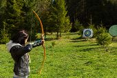 stock photo of archer  - Young girl archer. Shooting with a bow. ** Note: Soft Focus at 100%, best at smaller sizes - JPG