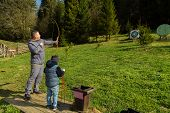 image of archery  - Father and son engaged in archery - JPG