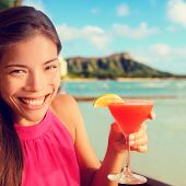 stock photo of waikiki  - Woman drinking cocktail alcohol drinks at beach bar resort in Waikiki - JPG