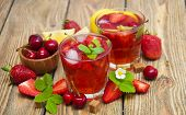 stock photo of cold drink  - Cold strawberry and cherries drink with fresh strawberriescherries and lemon on wooden background - JPG