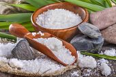 stock photo of salt-bowl  - salt bath in wooden bowl with bamboo leaves in background - JPG