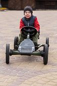 picture of car ride  - Boy riding a toy car  - JPG