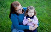 image of granddaughter  - Proud grandmother with her granddaughter sitting on the grass in the field - JPG