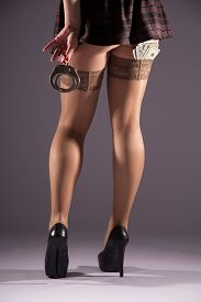 stock photo of stocking-foot  - Female prostitution violation of the law a fan of banknotes payment for services selling body for money the punishment for a crime immorality youth feet in nylon stockings - JPG