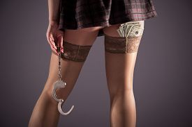 stock photo of stocking-foot  - Female prostitution violation of the law a fan of banknotes payment for services selling body for money the punishment for a crime immorality youth feet in nylon stockings steel handcuffs - JPG
