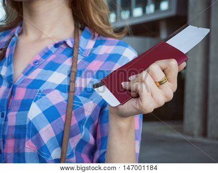 A young girl holds a passport and a plane ticket in his hand. The concept of tourism recreation vacation and travel.