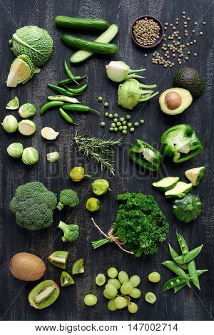 Variety of green vegetables produce on dark background flat lay savoy cabbage, avocado, brussel sprouts, kiwi, pepper, peas, lime part of green produce series
