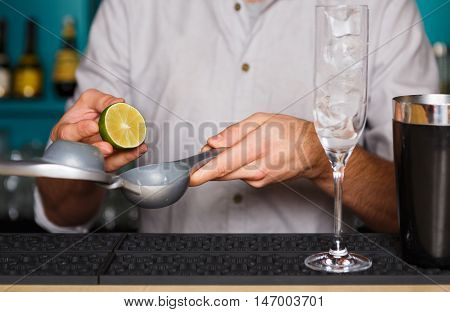 Barman's hands in bar interior making alcohol cocktail. Professional bartender at work in bar squeezing lime juice into mixing glass for citrus drink. Party time in night club