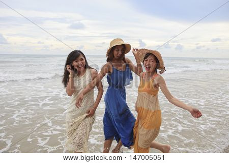 portrait of young asian woman with happiness emotion wearing beautiful dress walking on sea beach and laughing joyful use for people relaxing vacation on destination