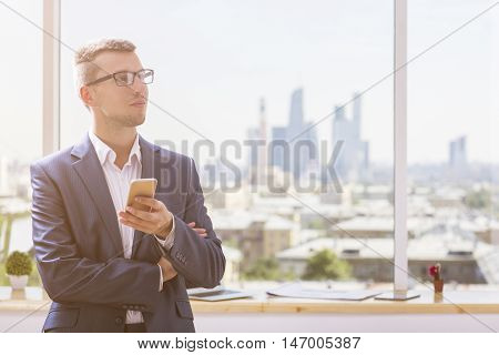 Portrait of attractive young businessman using mobile phone in modern interior with blurry items on windowsill and city view