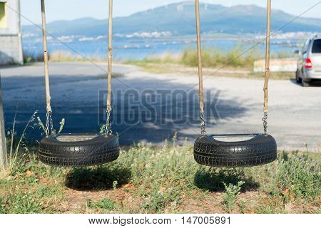 image of children's swings of tires outdoors
