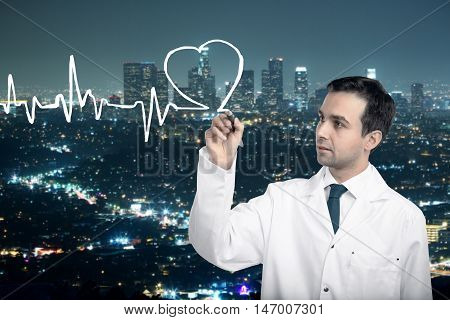Handsome caucasian male doctor drawing abstract cardiogram on illuminated night city background