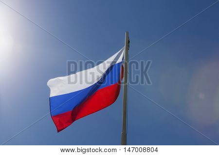 National flag of Russia on a flagpole in front of blue sky