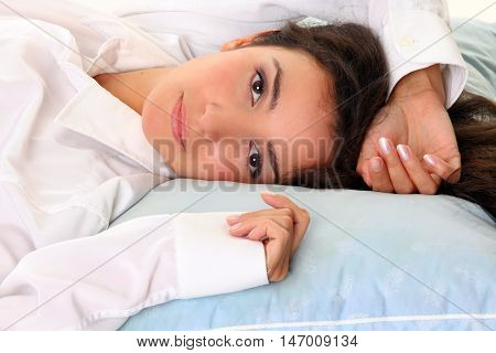 Happy Young Woman with dark hair In Bed