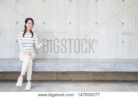 beauty woman smile and show something to you with white wall asian
