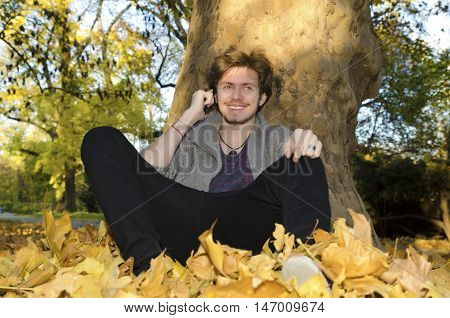 Teenager sitting under the tree among yellow leaves and talking on the mobile phone in the park