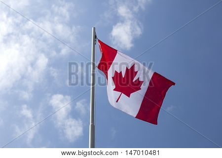 National flag of Canada on a flagpole in front of blue sky