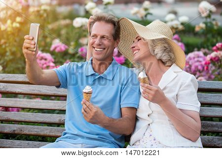 Man smiling and holding phone. Mature couple on a bench. Let me take a selfie. One of those priceless moments.