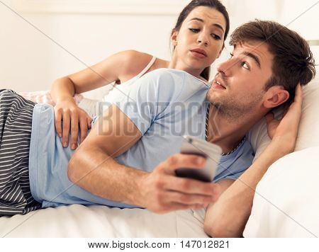 Addicted young man on bed texting  while woman looks angry