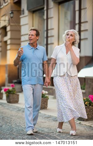 Couple holding hands. Mature woman eats ice cream. Best route for a stroll. Snack on the go.