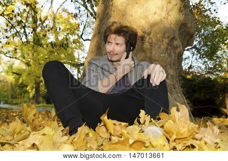 Teenager talking on a cellular phone under the tree in the park