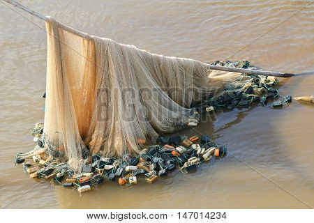Soft focus of Fishing net with multi color floats hanging on wooden bamboo stick