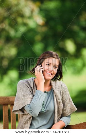 Beautiful Woman Phoning On The Bench