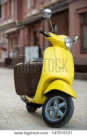 Brown suitcase on yellow scooter. Scooter on street background. Things are packed. Luggage for a small trip.