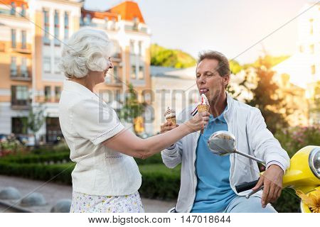 Adult man eats ice cream. Couple on street background. Let's make a short break. Trip to europe in summer.