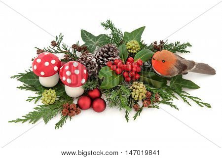 Christmas decorative display with robin, red baubles and fly agaric mushroom decorations with holly, ivy, snow covered pine cones and winter greenery over white background.