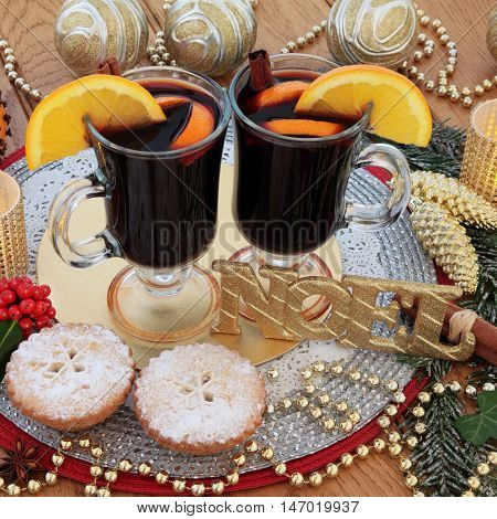 Christmas still life with gold glitter noel sign, mulled wine, mince pies, orange pomander, gold bauble decorations, candles, holly and snow covered fir on oak background.